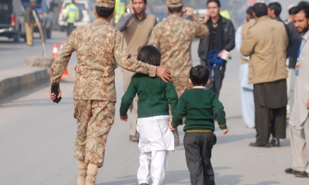 A Pakistani soldier escorts schoolchildren from the Army Public School after they were rescued. Source: Reuters