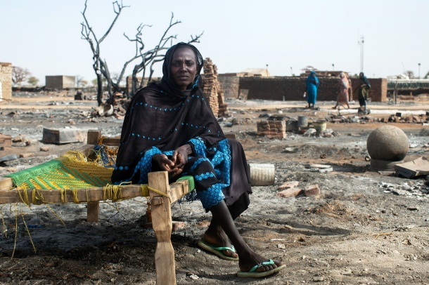 A displaced woman sits on a bed next to the remnants of her burnt house in Khor Abeche, South Darfur. April, 2014. Photo: Albert Gonzalez Farran, UNAMID (CC 2.0)